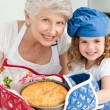 A little girl with her grandmother looking at the camera — Stock Photo #10843293