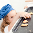 Little girl stealing cookies - Stock Photo