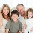 A happy family on their sofa looking at the camera — Stock Photo #10843332