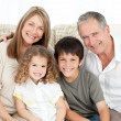 A happy family on their sofa looking at the camera — Stockfoto #10843334