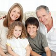 A happy family on their sofa looking at the camera — Stock Photo