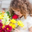 A little girl smelling  flowers — Stock Photo