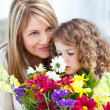 Little girl smelling flowers while her grandmother is smilling — Foto Stock
