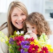 Little girl smelling flowers while her grandmother is smilling — Stok fotoğraf