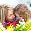 Little girl smelling flowers while her grandmother is smilling — Stock Photo