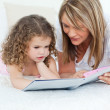 Young girl reading a book with her grandmother — Stock Photo