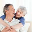 Senior couple hugging on their bed — Stock Photo #10843482