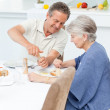 Retired couple eating in the kitchen — Stock Photo
