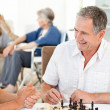 Men playing chess while their wifes are talking — Stockfoto
