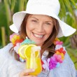 Royalty-Free Stock Photo: Retired woman drinking a cocktail under the sun