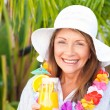 Retired woman drinking a cocktail under the sun — Stock Photo #10843543