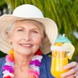 Retired woman drinking a cocktail under the sun - Lizenzfreies Foto