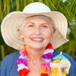 Retired woman drinking a cocktail under the sun - Stock Photo
