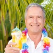 Mature man drinking a cocktail under the sun — Stock Photo