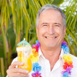 Mature man drinking a cocktail under the sun — Stock Photo #10843552