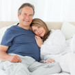 Senior couple lying down on their bed — Stock Photo