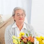 Senior woman with flowers — Stock Photo