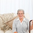 Mature woman sitting on the sofa with her walking stick — Stock Photo