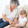 Grandmother helping her little girl to knit - Stock Photo