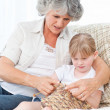 Grandmother helping her little girl to knit — Stock Photo #10844063