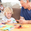 Little boy drawing with his grand father — Stock Photo