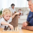 Young boy playing chess with his grandfather — Stock Photo #10844075