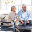 Lovely retired couple talking on the sofa — Stock Photo