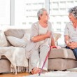 Mature friends talking on the sofa — Stock Photo