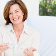 Cute mature woman with pills — Stock Photo