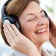 Foto Stock: Senior listening to music