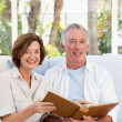 Seniors looking at their photo album at home - Stockfoto