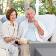 Seniors watching tv at home — Stockfoto