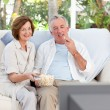 Seniors watching tv at home — ストック写真