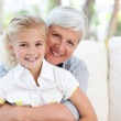 Lovely little girl with her grandmother looking at the camera — Stock Photo