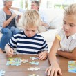 Children playing puzzle in the living room - Stockfoto