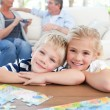 Children looking at the camera in the living room - Stockfoto