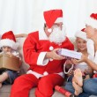 Santa Claus with a happy family — Stock Photo