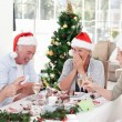 Seniors on Christmas day at home - Stock Photo