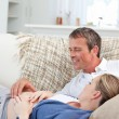 Couple lying down on the couch — Stockfoto