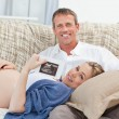 Couple looking at an X-ray on their couch at home — Stock Photo #10844984