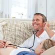 Man listening his wife's belly with his stethoscope — Стоковое фото