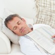 Exhausted man sleeping on the couch at home — Stock Photo