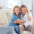 Stock Photo: Lovers watching tv in the living room at home