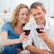 Couple drinking some red wine in the living room — Стоковая фотография