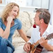 Romantic man playing guitar for her wife at home — Stock Photo