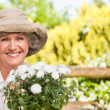 Smiling woman in her garden - Stock Photo