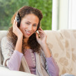 Radiant womlistening to music — Stockfoto #10845842