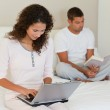Woman working on her laptop while her husband is reading — Stock Photo #10845987
