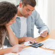 Young couple calculating their domestic bills - Stock Photo