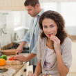 Woman eating while her husband is cooking — Stock Photo